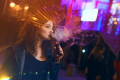 Red-haired girl smokes an electronic cigarette. Young attractive red-haired girl smokes electronic cigarette. She walks down street. Evening city lights and royalty free stock photos