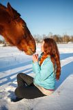Red-haired girl in a snowy field feeds an apple from hands stock photo