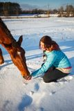 Red-haired girl in a snowy field feeds an apple from hands royalty free stock images