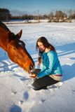 Red-haired girl in a snowy field feeds an apple from hands stock photos