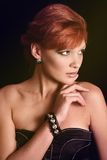 The red-haired girl with a speaking glance. With earrings and a bracelet Stock Photos