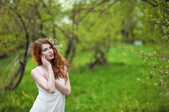 Red-haired girl in a spring garden Royalty Free Stock Photos