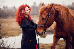 Red-haired girl stroking horse. Flower in her hair Stock Image