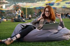 Red-haired girl student in glasses communicates on the phone and on the Internet, makes an order in the internet shop lying on a p royalty free stock images