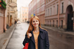 The red-haired girl in the style of casual walks in the city on Stock Photo