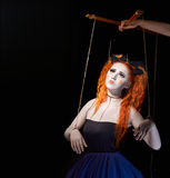 Red-haired girl stylized like marionette puppet. On black background Royalty Free Stock Image