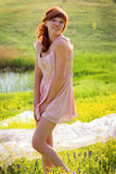 The red-haired girl in the sun on the meadow Stock Photography