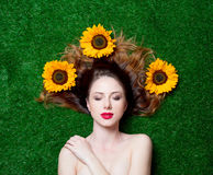 Red-haired girl with sunflowers on grass Stock Images