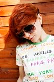 Red-haired girl in sunglasses. Portrait of red-haired girl in sunglasses with wooden wall behind royalty free stock photo