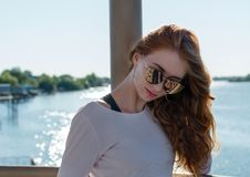 Red-haired girl in sunglasses on background of the river Royalty Free Stock Image