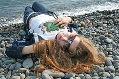 Red-haired girl with sunglasses lies on the pebble beach Royalty Free Stock Images