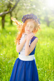 Red-haired girl in a sunny garden Royalty Free Stock Photos