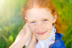 Red-haired girl in a sunny garden Royalty Free Stock Photo