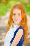Red-haired girl in a sunny garden Royalty Free Stock Image