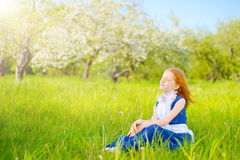 Red-haired girl in a sunny garden Royalty Free Stock Images