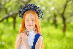 Red-haired girl in a sunny garden stock images