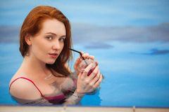 The red-haired girl in a swimsuit standing in a pool. In the hands holding a glass of cold orange juice. Royalty Free Stock Photography