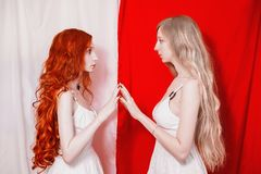 Red-haired Girl Touched The Blonde. Unity Of Red And White. Two Fabulous Young Girl With Long Curly Hair. Stock Photography