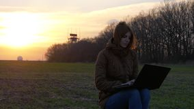 A red-haired girl uses laptop near radar in field stock video footage