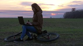 A red-haired girl uses laptop near radar in field during sunset on bicycle. Young red-haired girl uses laptop near radar and communication equipment station in stock footage