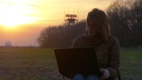 A red-haired girl uses laptop near radar in field during sunset stock footage