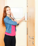 Red-haired girl using house videophone indoor. Red-haired girl using house videophone royalty free stock images