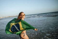 Red-haired girl wearing Brazilian flag in water on beach Royalty Free Stock Photography