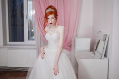 Red-haired girl in a wedding dress, bright unusual appearance, red nails, a girl with pale skin. Beautiful wedding dress, a heart on her cheek, bright make-up stock images