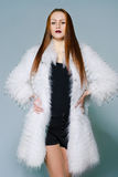 Red-haired girl in a white fur coat, studio portrait, light background Stock Photography
