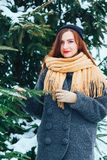 Red-haired girl in a winter forest near a Christmas tree Royalty Free Stock Photos