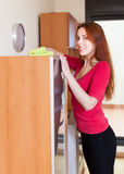 Red-haired girl wiping the dust from  furniture Royalty Free Stock Images