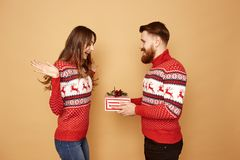 Red-haired guy gives a Christmas gift to a girl both are dressed in red and white sweaters with deer and stands on a stock photography