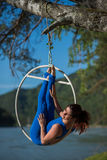Red-haired gymnast in a blue suit doing the difficult exercises at the air ring in nature. Red-haired gymnast in a blue suit doing the difficult exercises at the Stock Photos