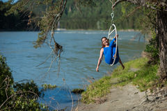 Red-haired gymnast in a blue suit doing the difficult exercises at the air ring in nature. Red-haired gymnast in a blue suit doing the difficult exercises at the Royalty Free Stock Images