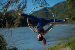 Red-haired gymnast in a blue suit doing the difficult exercises at the air ring in nature. Red-haired gymnast in a blue suit doing the difficult exercises at the Stock Photo