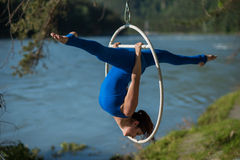 Red-haired gymnast in a blue suit doing the difficult exercises at the air ring in nature. Red-haired gymnast in a blue suit doing the difficult exercises at the Royalty Free Stock Photography