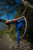 Red-haired gymnast in a blue suit doing the difficult exercises at the air ring in nature. Red-haired gymnast in a blue suit doing the difficult exercises at the Royalty Free Stock Photo
