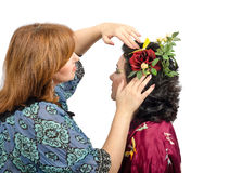 Red-haired hairstylist putting in a red rose in her hair customer stock images