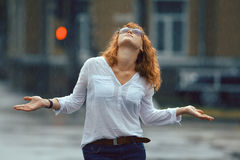 Red-haired happy woman in the rain. Portrait of red-haired happy woman in the rain Royalty Free Stock Images