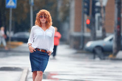 Red-haired happy woman in the rain. Portrait of red-haired happy woman in the rain Royalty Free Stock Photos