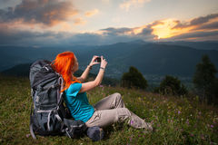 Red-haired lady with backpack in the mountains at sunset Royalty Free Stock Photo