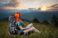 Red-haired lady with backpack in the mountains at sunset Stock Images