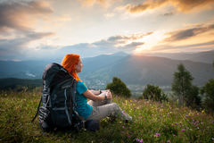 Red-haired lady with backpack in the mountains at sunset Stock Image