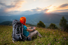 Red-haired lady with backpack in the mountains at sunset royalty free stock photography