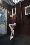 Red haired lady hanging on fire escape in swimsuit Royalty Free Stock Photos