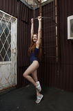 Red haired lady poses near fire escape in swimsuit Royalty Free Stock Photography