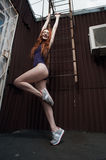 Red haired lady poses near fire escape in swimsuit Stock Photos