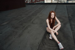 Red haired lady poses on the roof in swimsuit Royalty Free Stock Photography