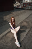 Red haired lady poses on the roof in swimsuit Royalty Free Stock Images