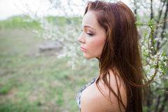 Red-haired lady in spring orchard near blooming trees Royalty Free Stock Image